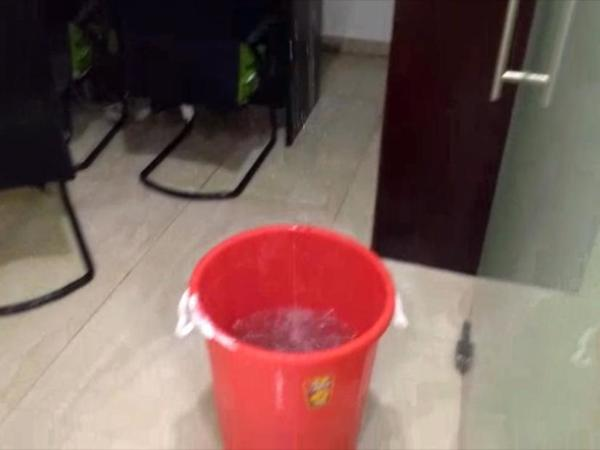 Office staff placed bucket under the leaking roof
