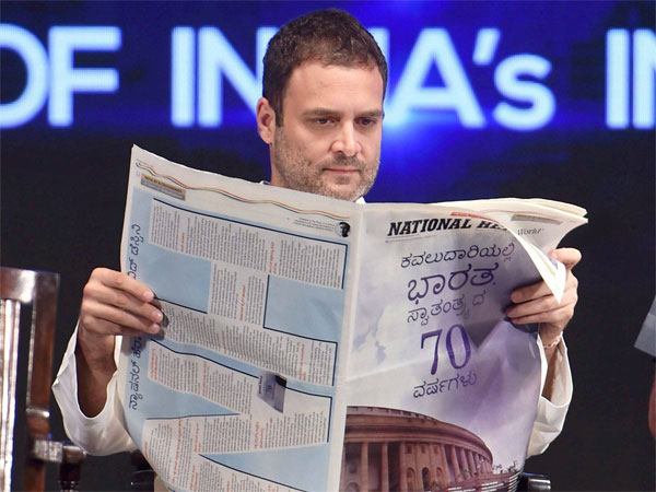 Congress Vice President Rahul Gandhi goes through the pages of National Herald newspaper during the launch of its commemorative edition in Bengaluru