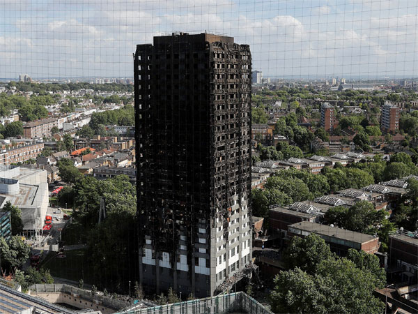 Theresa May takes cover from crowds on Grenfell Tower visit