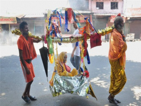 Devotees carrying a woman in a Kanwar in Moradabad