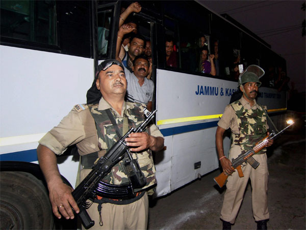 Security personnel stand guard near a bus with Amarnath pilgrims. Photo credit: PTI