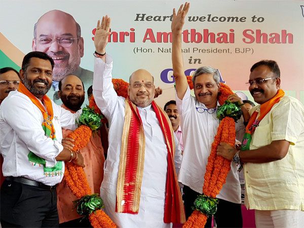 BJP national President Amit Shah with Goa Chief Minister Manohar Parrikar being garlanded at Dabolim airport upon Shah's arrival on Saturday. PTI Photo