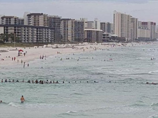 Strangers form a human chain to help save nine people caught in rip current.