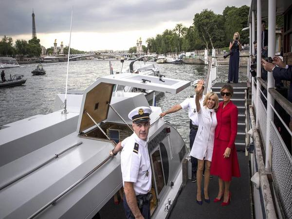 US First Lady Melania Trump, right, and French president's wife Brigitte Macron wave after a boat trip down the River Seine in Paris