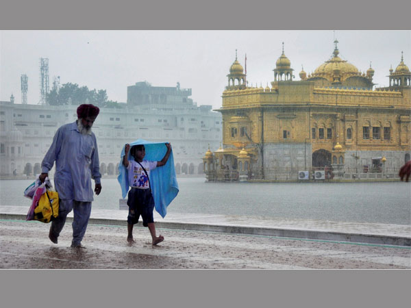 Devotess walking at Golden Temple during heavy rainfall in Amritsar. PTI file photo