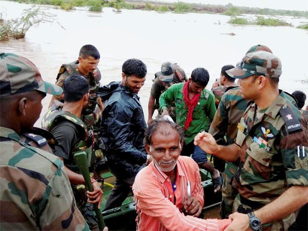 Army personnel rescue villagers, who were stuck in the flooded villages due to heavy downpour at Surendranagar district, in Gujarat