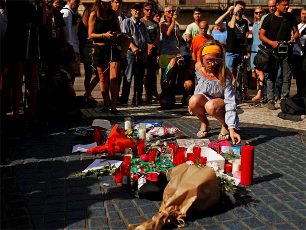 A woman places a postcard of the Barcelona's Sacred Family cathedral next to bunches of flowers in Las Ramblas, Barcelona, Spain, Friday, Aug. 18, 2017. Police on Friday shot and killed five people carrying bomb belts who were connected to the Barcelona van attack, as the manhunt intensified for the perpetrators of Europe's latest rampage claimed by the Islamic State group. PTI photo