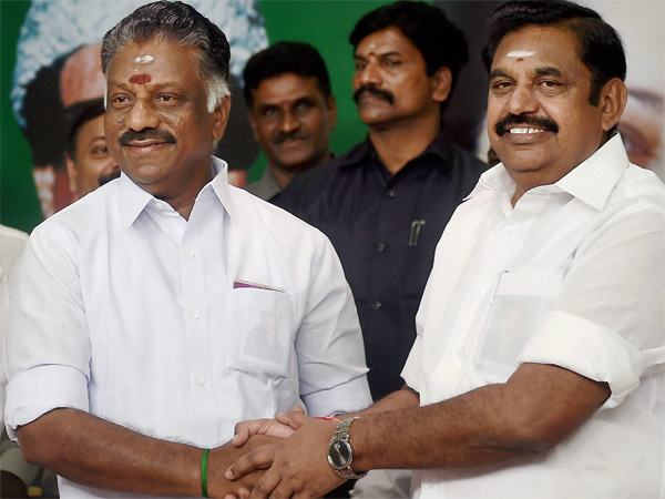 Tamil Nadu Chief Minister K Palaniswami (R) and O Panneerselvam exchange greetings following merger of their factions in Chennai