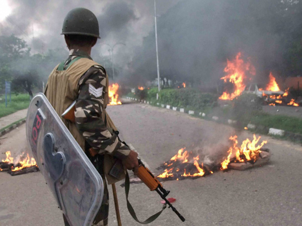 A Security personnel stands towards vehicles burning in violence following Dera Sacha Sauda chief Gurmeet Ram Rahim's conviction in Panchkula on Friday. PTI Photo