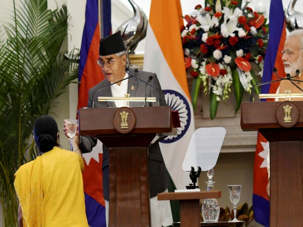 External Affairs Minister Sushma Swaraj offers a glass of water to Nepalese Prime Minister Sher Bahadur Deuba