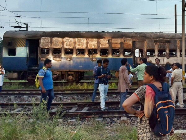 People stand near a vandalized train coach in Anand Vihar Sation in New Delhi on Friday. Photo credit: PTI