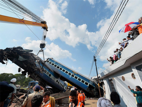 A mangled coach of the Puri-Haridwar Utkal Express train being hauled off the tracks by a crane, at the accident site in Khatauli near Muzaffarnagar