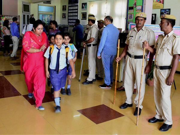 Parents take their children home after the murder of a class 2 student at Ryan International School as a police team looks on, in Gurugram