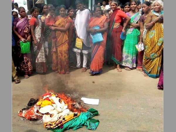 Women burn saris after a clash between two groups over the shortage of stock