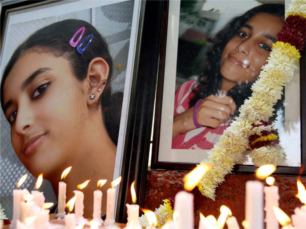 In this file photo friends and relatives of Aarushi Talwar light candles near her portrait.
