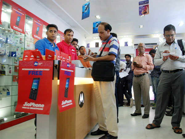 People filling forms to buy JIO mobile phones in New Delhi