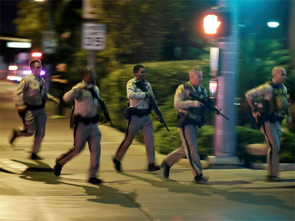 Police run to cover at the scene of a shooting near the Mandalay Bay resort and casino on the Las Vegas Strip, Sunday, Oct. 1, 2017, in Las Vegas. Multiple victims were being transported to hospitals after a shooting late Sunday at a music festival on the Las Vegas Strip. AP/PTI