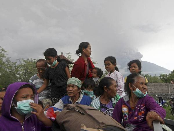 Villagers sit on a truck during evacuation