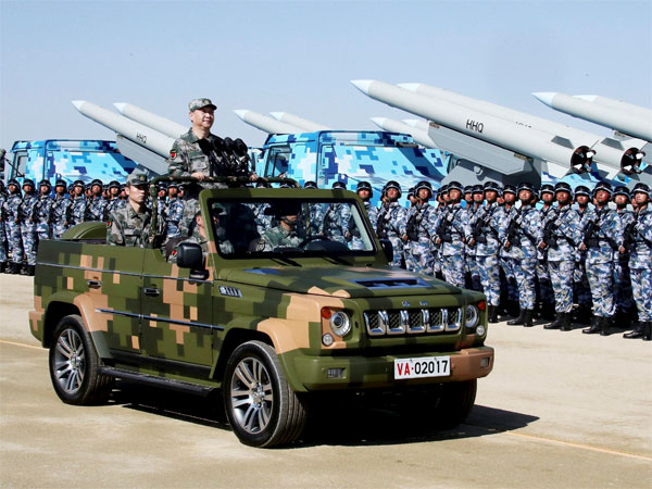 Chinese President Xi Jinping stands on a military jeep as he inspects troops of the People's Liberation Army during a military parade