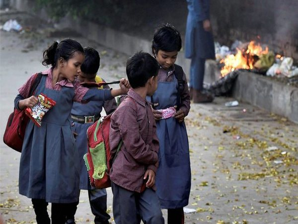 Schoolchildren walk past a man standing near a fire, at a pavement in New Delhi on Monday. Schools in Delhi reopened on Monday following four-days of closure due to smog and air pollution. PTI Photo