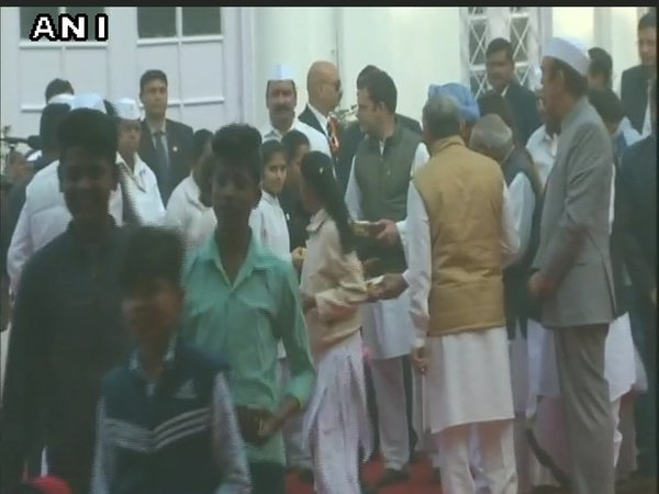 Rahul distributing sweets to children