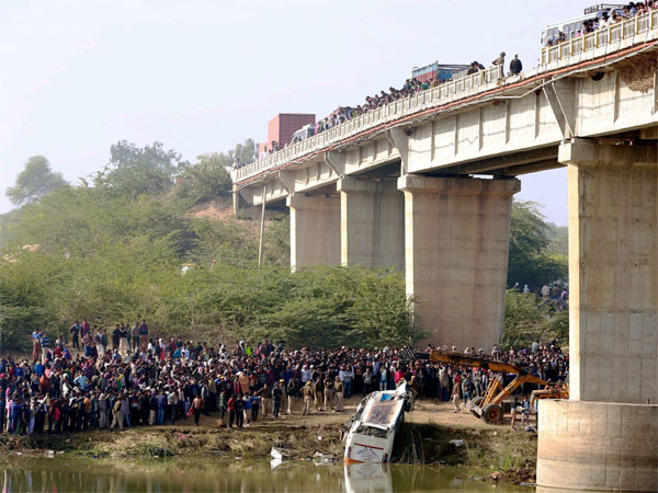 People gather after a passenger bus fell off a bridge in Banas river in Sawai Madhopur's Dubi area in Rajasthan on Saturday. At least 33 people died and several injured in this accident. PTI Photo