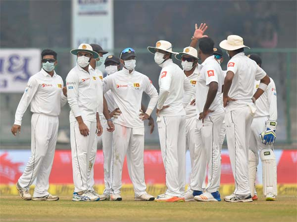 Sri Lankan players wear anti-pollution masks on the field as the air quality deteriorates during the second day of their third test cricket match against India in New Delhi