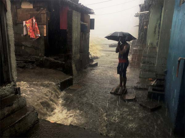 A man stand with an umbrella in a street amid heavy showers triggered by cyclone Ockhi