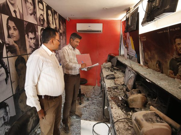 Forensic experts examine the ticket counter of a cinema hall after it was vandalised in Ahmedabad