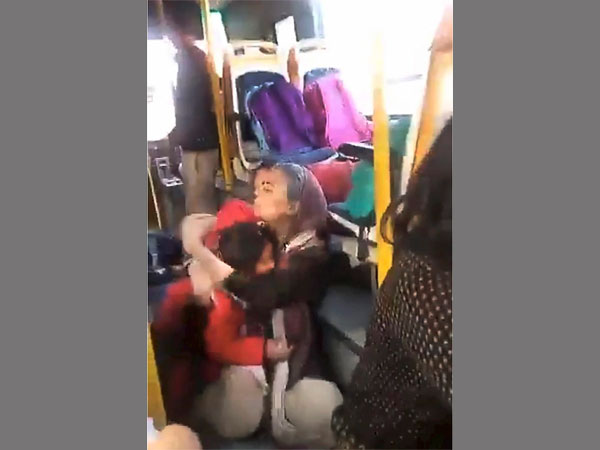 A woman hugs a child crouched on the floor of the GD Goenka World School bus, as a mob protesting against the film 'Padmaavat' threw stones at their bus in Gurugram