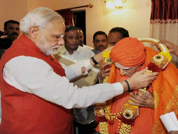 Prime Minister Narendra Modi offers a garland to Sri Shivakumar Swamyji during his visit to the Siddaganga Mutt in Tumkur. PTI file photo