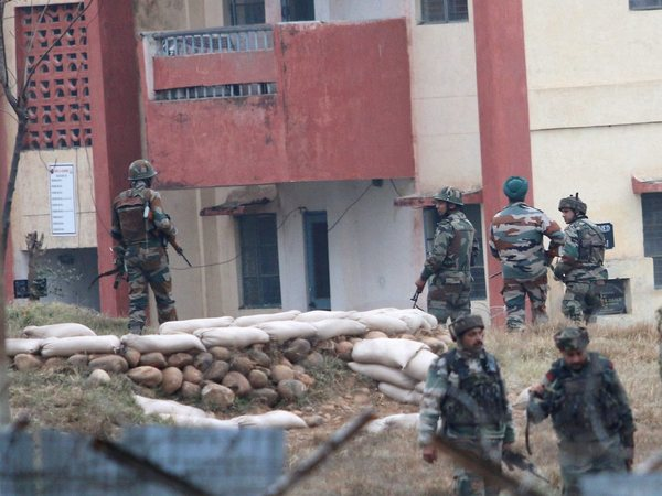 Security personnel take position around the army family quarters at Sunjuwan Military Station during the terrorist attack, in Jammu on Sunday. PTI Photo