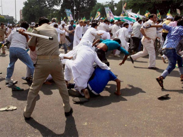Policemen chasing away Peace Party activists protesting against Muzaffarnagar riots, in Lucknow (2013). PTI file photo