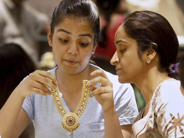 A girl tries a gold necklace inside a jewellery showroom