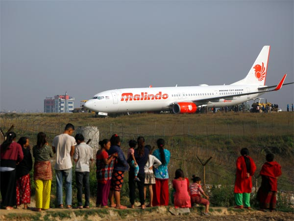 People watch a Malindo Air passenger plane after it skidded to the grassy area at the end of runway in Tribhuwan International Airport in Kathmandu, Nepal