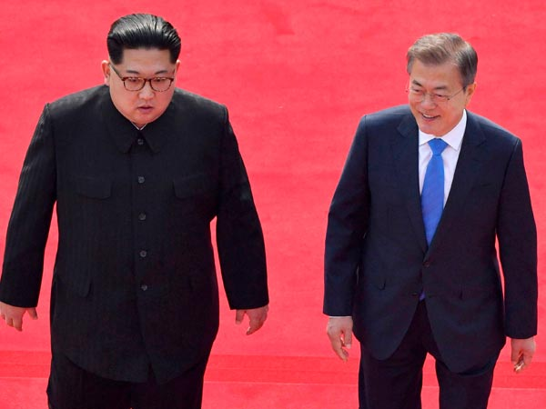 North Korean leader Kim Jong Un, left, and South Korean President Moon Jae-in walk toward the Peace House for their meeting at the border village of Panmunjom