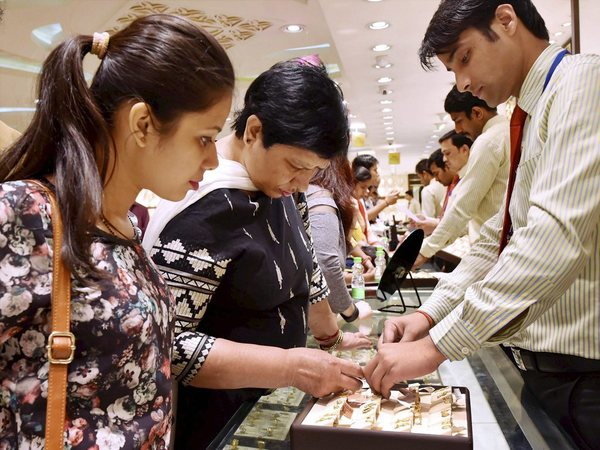A woman buys gold jewellery in a shop on the occasion of Akshaya Tritiya