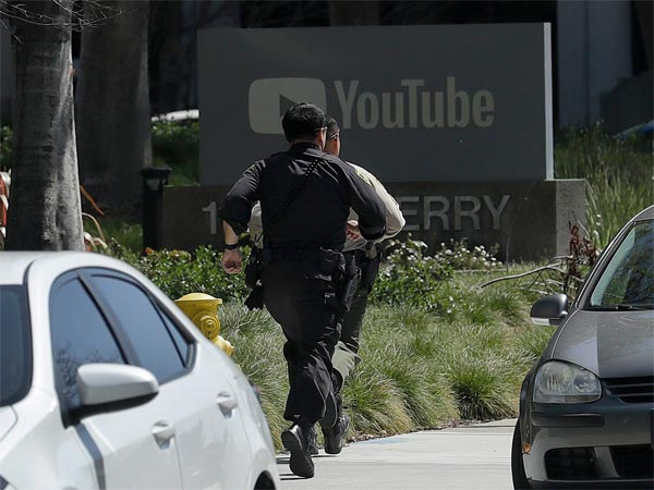 Officers run toward a YouTube office in San Bruno