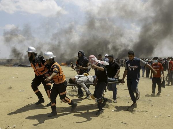 Palestinian medics and protesters evacuate a wounded youth during a protest at the Gaza Strips border with Israel, east of Khan Younis, Gaza Strip, Monday, May 14, 2018. Thousands of Palestinians are protesting near Gazas border with Israel, as Israel prepared for the festive inauguration of a new U.S. Embassy in contested Jerusalem. AP/PTI