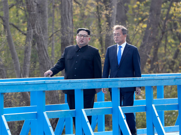 North Korean leader Kim Jong Un, left, and South Korean President Moon Jae-in talk as they walk on a footbridge at the border village of Panmunjom in the Demilitarized Zone, South Korea