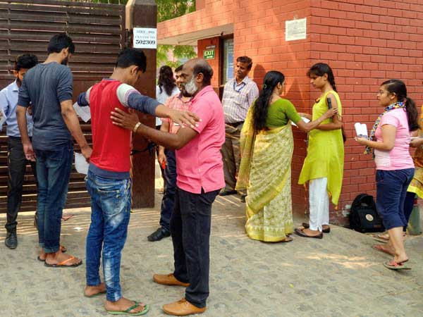 Applicants undergo security check outside the examination centre for the NEET Exam.