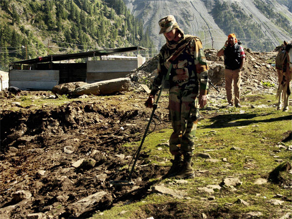 An army man checks a base camp with a metal detector at Amarnath Yatra route in Baltal
