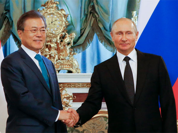 Russian President Vladimir Putin, right, and South Korean President Moon Jae-in shake hands during a meeting at the Kremlin in Moscow, Russia