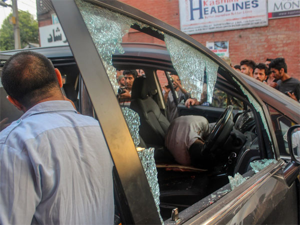 Police and locals inspect the damaged vehicle after suspected militants attacked senior journalist Shujaat Bukhari and his PSOs, at Press Colony in Srinagar