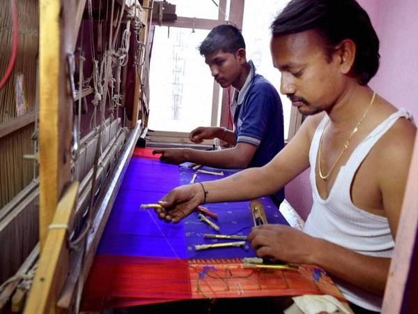 Workers prepare a handwoven Saree made from very fine silk. PTI file photo