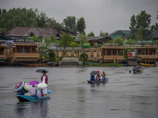People cross Dal Lake