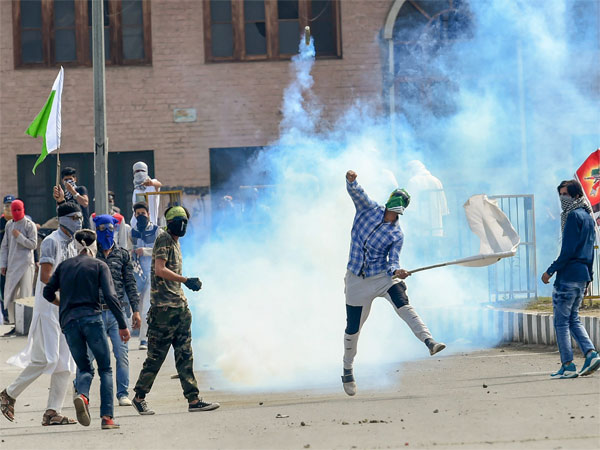 A protester throws an exploded tear gas shell back at police and CRPF during a clash, which erupted after youth staged a protest march soon after Eid-ul-Fitr prayers in Srinagar