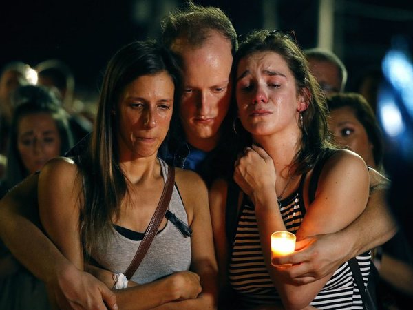 Mallory Cunningham, left, Santino Tomasetti, center, and Aubrey Reece attend a candlelight vigil in the parking lot of Ride the Ducks Friday, July 20, 2018, in Branson, Mo. One of the companys duck boats capsized Thursday night resulting in over a dozen deaths on Table Rock Lake. AP/PTI