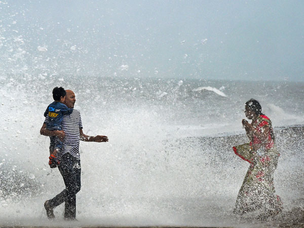 People react during a high tide at the Worli seaface, in Mumbai