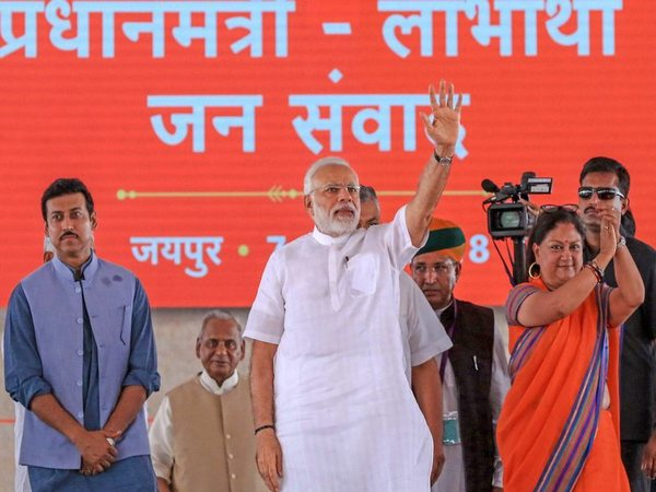 Prime Minister Narendra Modi waves to the beneficiaries of various welfare schemes of the BJP government, at a meeting in Jaipur on Saturday, July 7, 2018. Rajasthan Chief Minister Vasundhara Raje and Union minister Rajyavardhan Singh Rathore are also seen. PTI photo